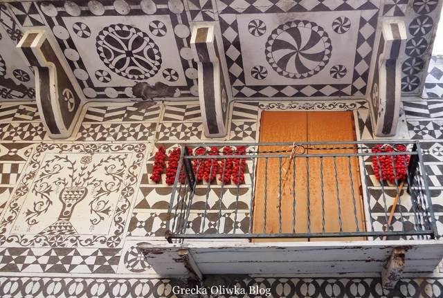 wzorzysty balkon i fasady dodatkowo ozdobione wiszącymi sznurami pomidorów