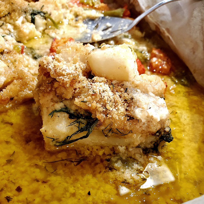 this is a pan of haddock topped with scallops in a lemon dill butter sauce and sprinkled with toasted breadcrumbs