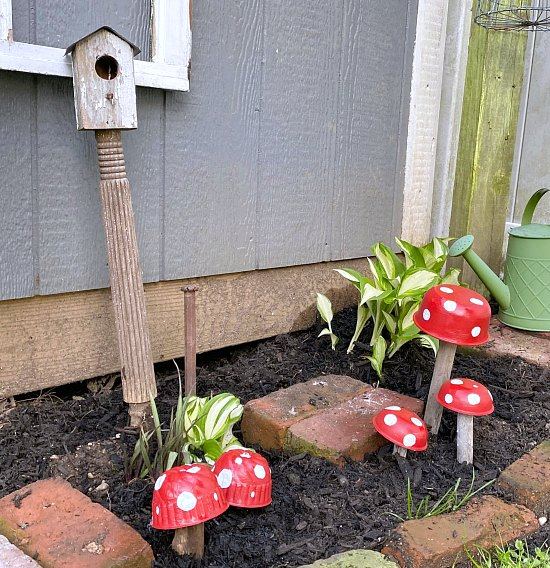 Repurposed Garden mushrooms in garden with birdhouse