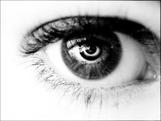 Μάτι γυναίκας, μαύρου χρώματος. Ακολουθεί το κείμενο: Τὰ μάτια σου, πουλάκι μου μελαχροινό, ποὺ φῶς μέσ᾿ στὶς καρδιὲς σταλάζουν, μὲ τ᾿ ἄστρα τὰ ψυχρὰ ψηλὰ στὸν οὐρανό, -μὴ σὲ γελοῦν οἱ ποιηταί- δὲ μοιάζουν.     Τ᾿ ἀστέρια κάθε μαύρη νύχτα φωτεινά μὲ καλωσύνη λάμπουν στὰ πελάγη τὰ βλέπει ὁ ναύτης, ποὺ μὲ γνῶσι κυβερνᾷ καὶ ἴσιο δρόμο λάμνει ἐκεῖ ποὺ πάγει.     Τὰ μάτια σου τὰ μαῦρα, φῶς μου, ὅποιος τὰ ἰδῇ, τόσες γλυκάδες καὶ φωτιὲς γεμάτα, ἂν εἶναι καὶ τὸ γνωστικότερο παιδί, θὲ νἄβγη ὀπὸ τὴν ἴσια του τὴν στράτα.