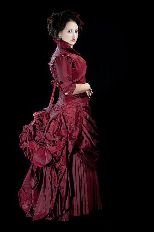 woman wearing a scarlet red neo-victorian bustled gown in silk taffeta (skirt, corset bodice, bolero jacket)