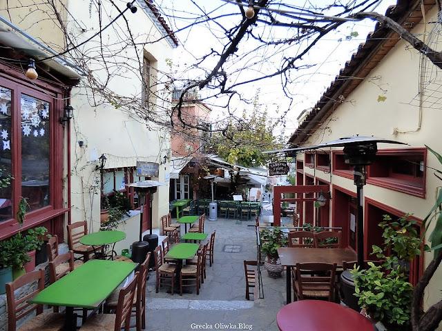 pod bezlistnym konarem drzewa na jednej z ateńskich uliczek znajdują się brązowe stoliki z zielonym blatem, obok latarenki