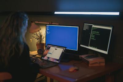 """صورة لفتاة تعمل على الكمبيوتر المحمول """" اللابتوب """" وأمامها أيضا شاشتين كمبيوتر عادي"""