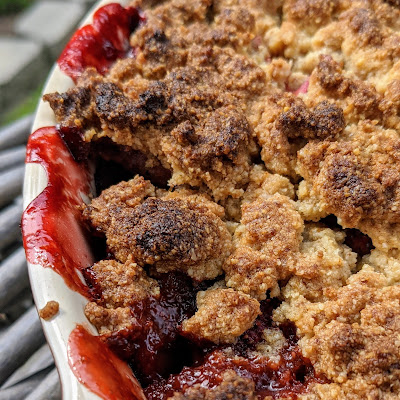Overhead view of crumble, cropped to one side, red juices and browned crumbles.
