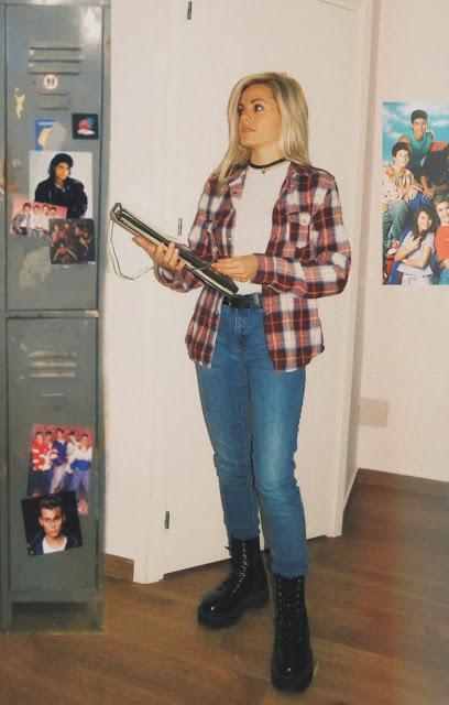 Estilo de los años 90 con suéter blanco bajo una camisa de cuadros, pantalón vaquero y botas negras, inspirado en EGB con edición de fotos estilo 80's/90's