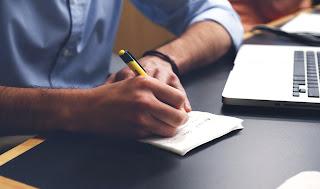 homem em sua mesa de escritório anotando algo em um bloco de notas