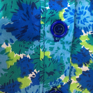 A big blue button against a blue and green floral background.