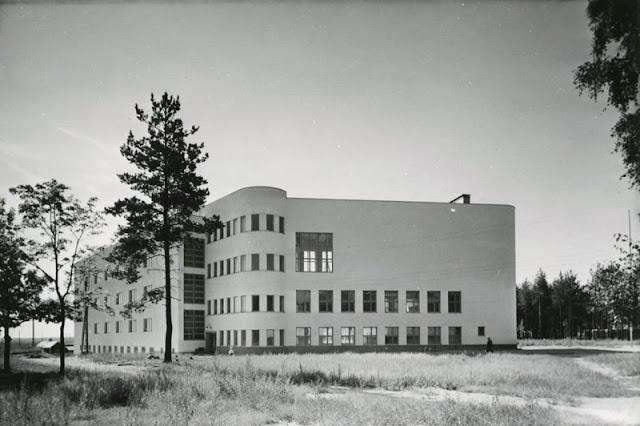 Mustavalkoinen maisemakuva, jossa kuvan keskiössä suuri valkoinen rakennus.