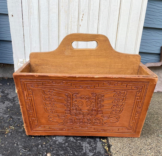 Photo of a vintage magazine holder with tooled leather exterior