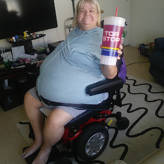 Karon poses on her wheelchair,  holding up a soft drink refill she got on her own.