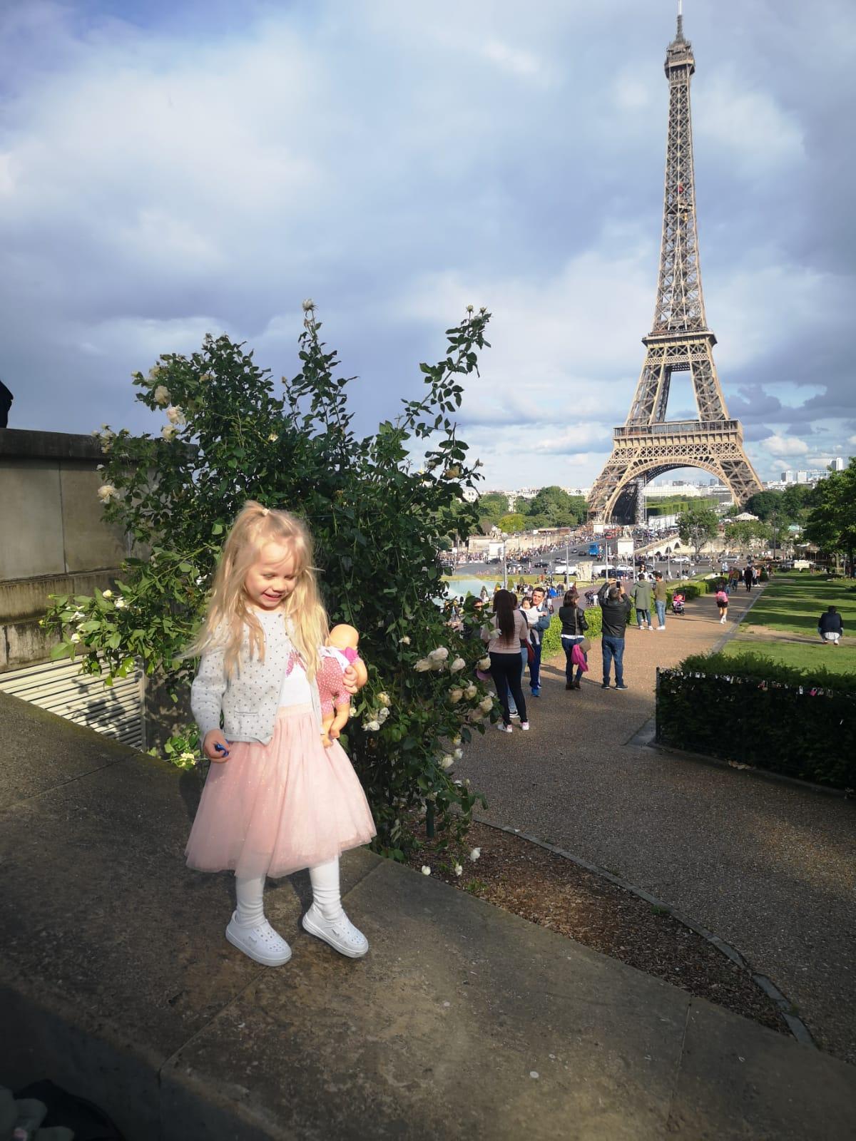 tuleva iso-sisko Eiffel-tornin edessä vauvanukkensa kanssa