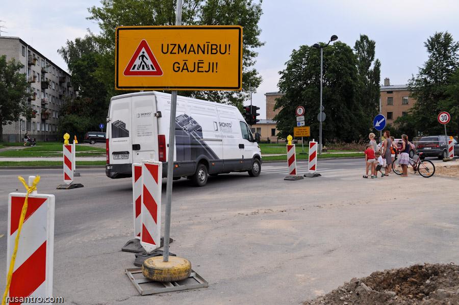 Ceļa zīme brīdina par gājējiem uz gājēju pārējas remontdarbu vietā