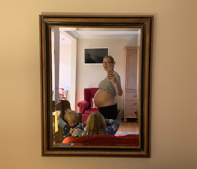 A mobile photo take on 38 week pregnant bump in a mirror with children in the foreground