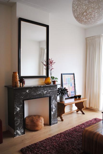 Boven een donkergrijze marmeren schouw hangt een grote spiegel met zwarte rand. Op de mantel staan vazen in rood en okergeel en ernaast staat een houten tafeltje. In het hart van de haard een lichtbruine leren poef.