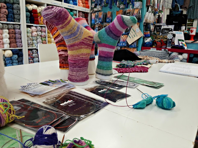 A photo showing four pairs of socks on foot forms standing on a table.  In the foreground is some knitting on needles in turquoise yarn and a selection of packets of knitting needles