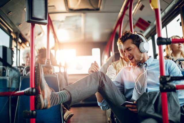 Guy on a bus commute listening to music and having fun