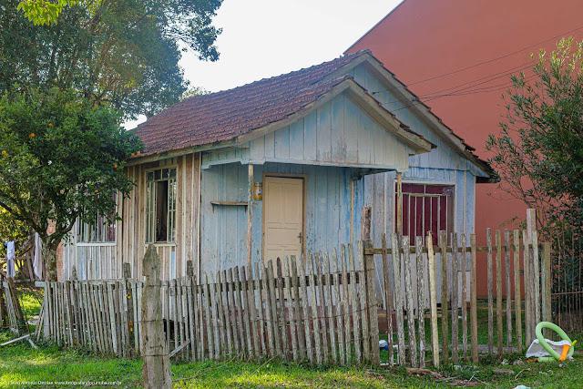 Casa de madeira com um pé de vergamota na lateral