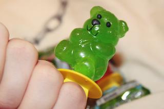 a green candy bear finger friends oversized green teddy bear ring being worn
