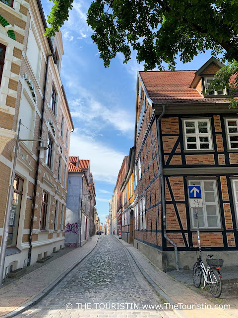 A white bicycle parks at the start of a cobblestone lane lined by three-storey timbered houses.