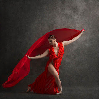 A Beautiful Ballet Dancer in Motion Wearing a Red Dress and Holding Flowing Red Silk Fabric Through the Air