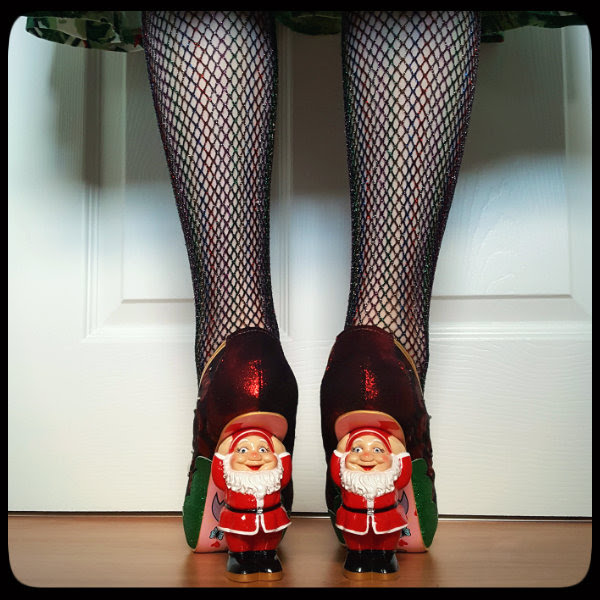 wearing shimmering fishnets and shoes with Santa character heels
