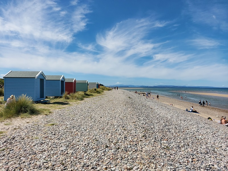 Row of colourful beach huts on a pebbled beach alongside sand and sea