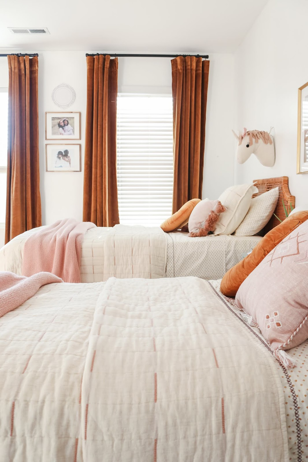 A boho shared bedroom for girls with rattan beds and luxe curtains