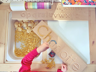 wooden name board with pasta and beads filling the letters