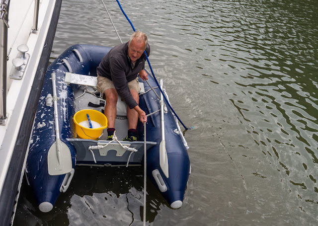 Photo of Phil pulling himself along the side of Ravensdale using the rope that was holding the dinghy in