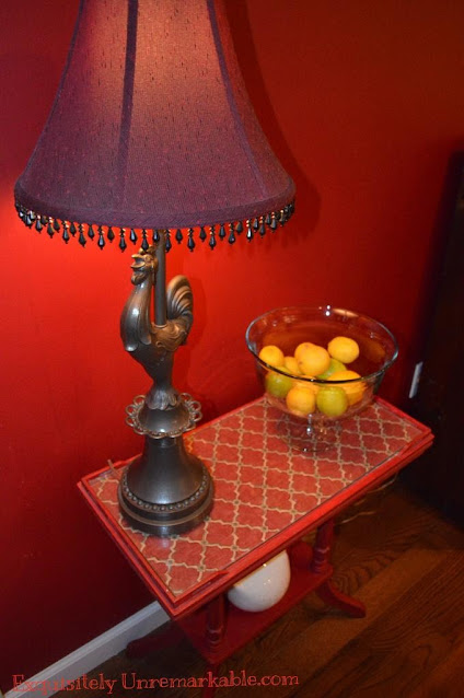Red table with red and green fabric under glass and lemons on top