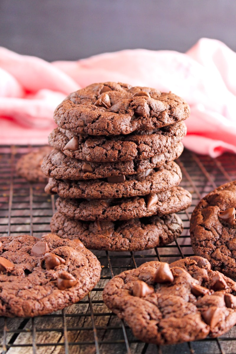 Side view of a stack of Triple Chocolate Cake Mix Cookies on a cooling rack on a wood surface.