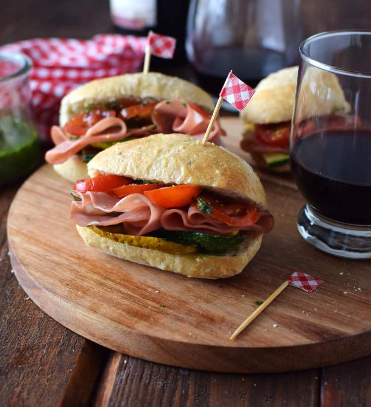 Sándwich con pan rústico semi integral, embutido de mortadela y tomate con vinagreta de albahaca