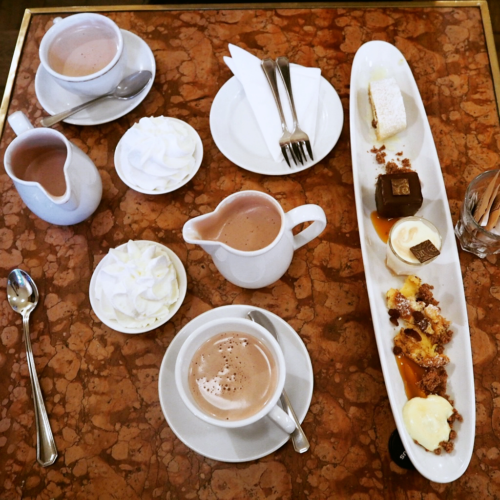 plate of cakes and mugs of hot chocolate