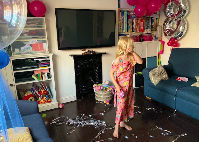 A living room with lots of toys, blue sofas, dark hard wood floors, balloons and silver streamers with an 8 year old in party clothes in the middle of the room