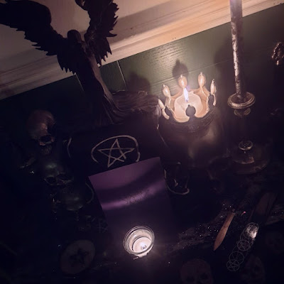 A photograph of 2019's Samhuinn altar taken from an oblique angle. At the left of the altar is a stack of three resin skulls, at the right of the altar is a large resin skull, approximately life-size, which is crowned and the crown serves as a candle-holder for a large-ish white candle. In the centre of the image is a stand with a black altar-cloth with white pentacles, upon which is a black resin statue of the Goddess Badb with flowing black robes and large out-stretched wings. At the front of the stand is a purple card with a sigil on it. At the front of the altar is a small black skull-shaped candle-holder with ornament and in-set glass containing a light grey tealight. The base altar-cloth is silver, black and grey - a scarf with a woven leaf pattern. At the right side of the altar is an athame dagger with a brass leaf-shaped blade and a wooden handle.
