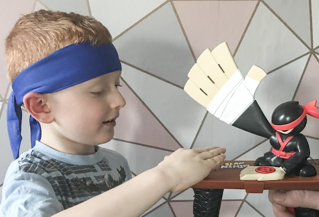 Little boy with a ninja head tie around his head playing with the chop option game