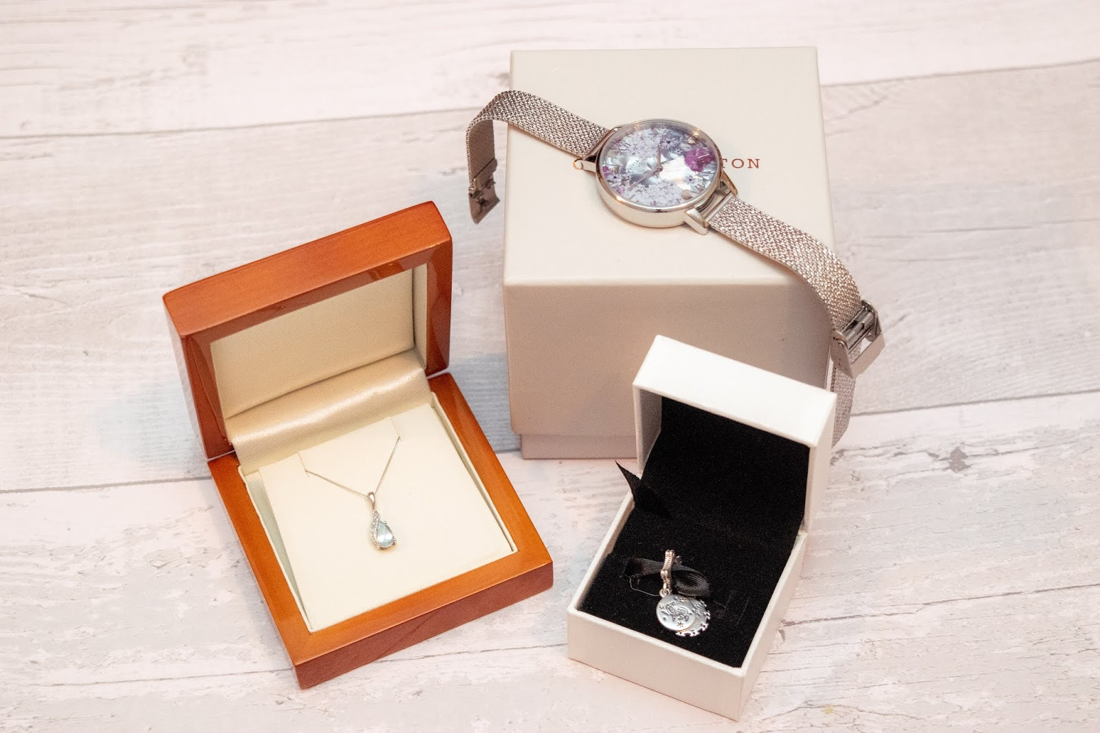Jewellery gifts gathered together: a necklace, watch and charm.