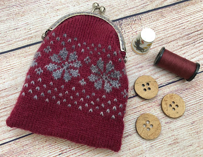 Coin purse knitted with DROPS Fabel Ruby Red and Silver Fox and closed with metal frame with kiss clasp lock