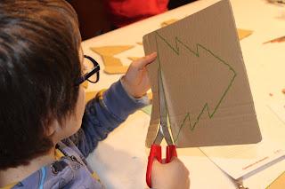 criança a cortar o desenho de uma árvore de Natal em cartão