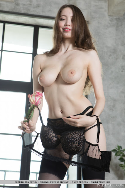 Erotic girl Suok B gets topless in black lingerie