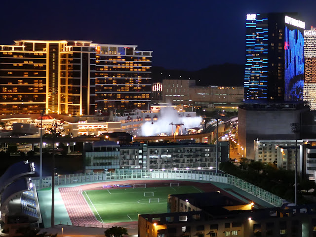 cable car passing in front of Wynn Palace's Performance Lake at night seen from afar
