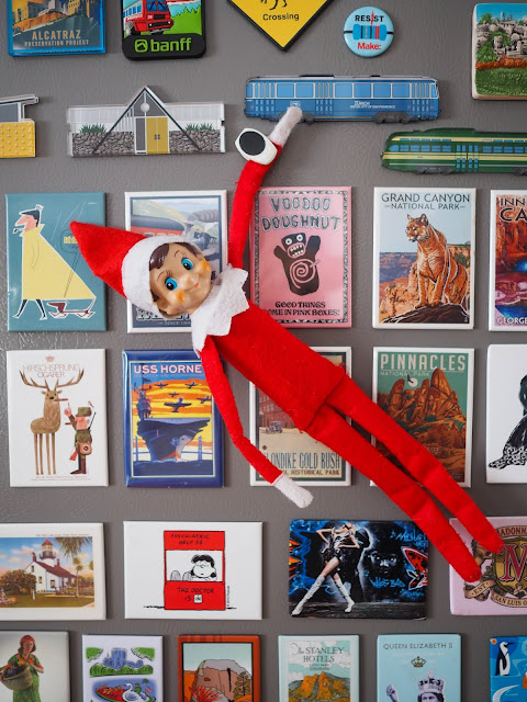 Elf on the Shelf hanging among fridge magnets