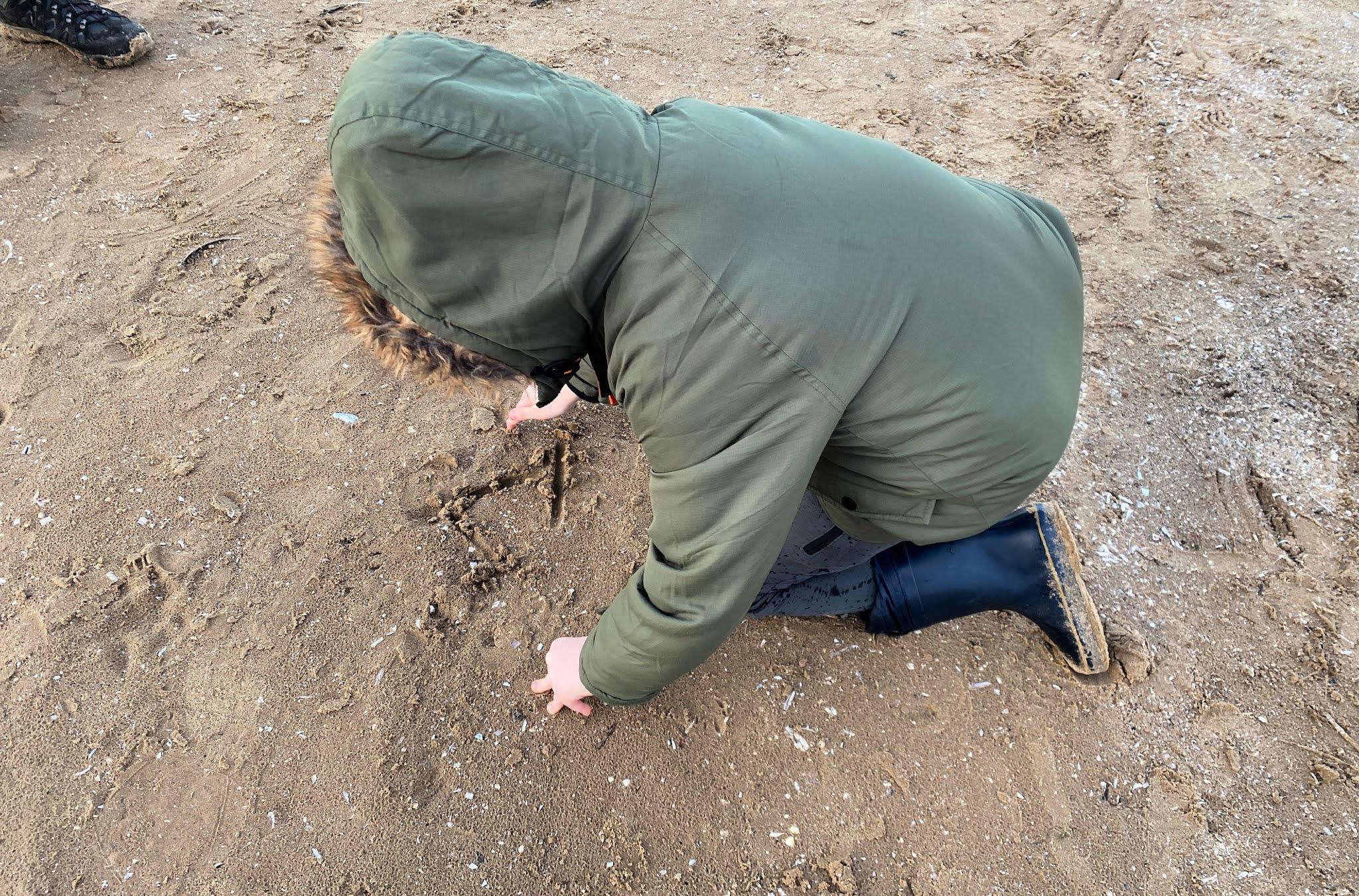 boy writing name in sand