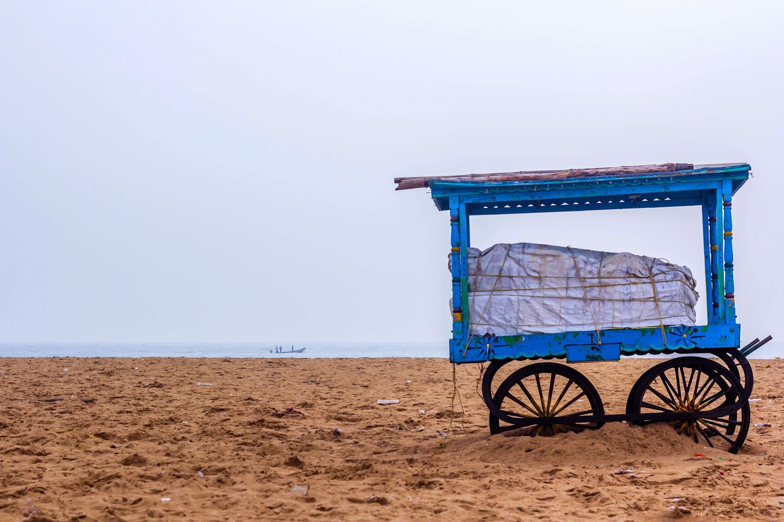Photo of a cart with a roof on it which is used to set-up shop in Chennai beach. Photo taken on a cloudy day.