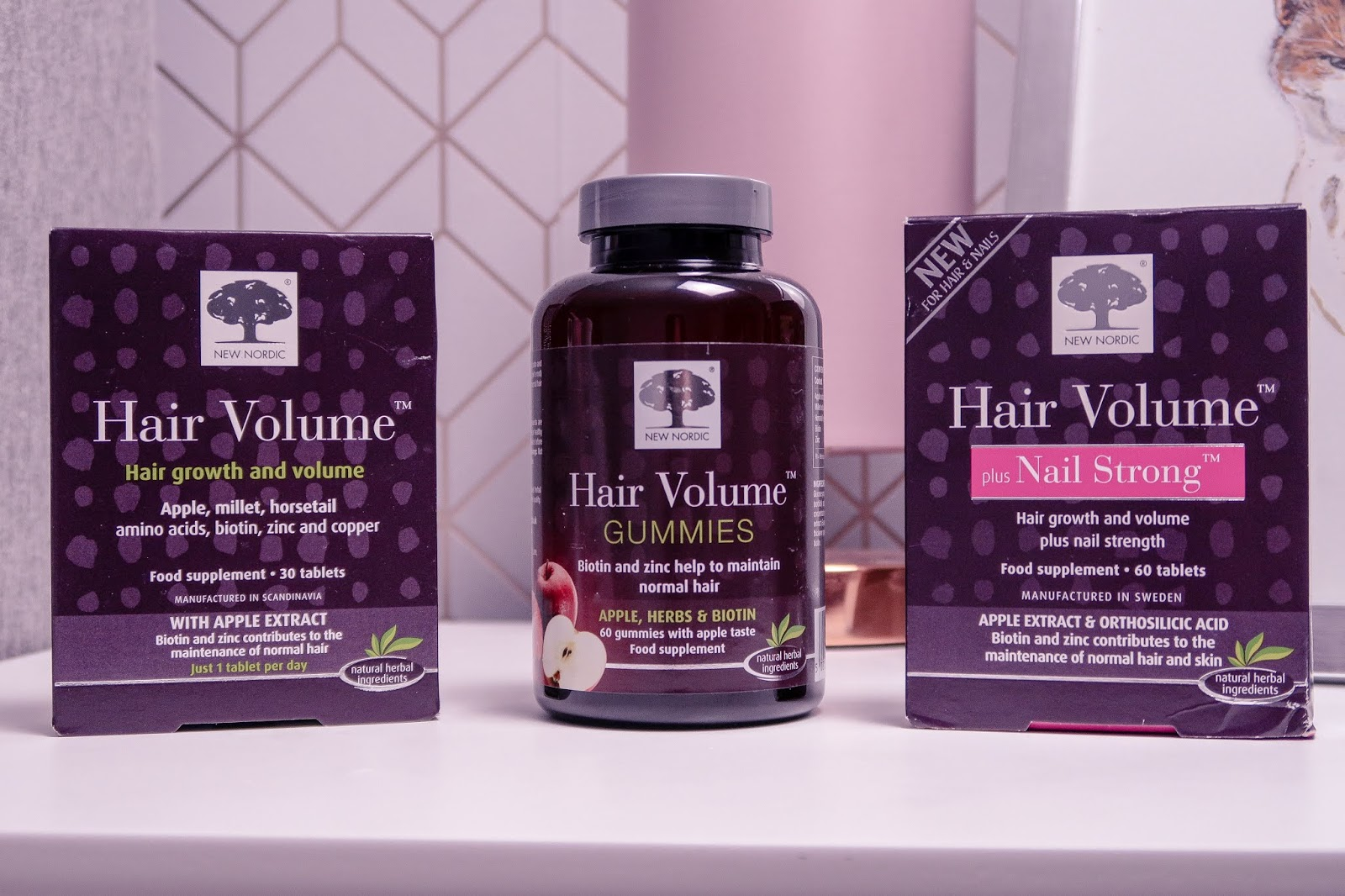 Close up photo of two New Nordic Hair Volume Supplements plus Hair Volume gummies bottle places on a white bed side table with a baby pink lamp in the background out of focus. Bottle plus boxes are Purple with white writing.