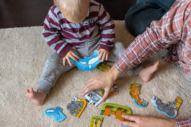 A Dad and son looking at the pieces of the Orchard Toys puzzle they were sent to review