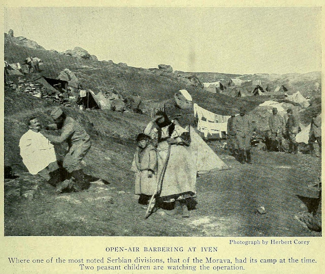 OPEN-AIR BARBERING AT IVEN Where one of the most noted Serbian divisions, that of the Morava, had its camp at the time. Two peasant children are watching the operation.