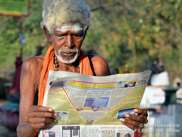 Matt Hahnewald Photography; Facing the World; closeup; street portrait; outdoor; candid; Asia; South Asia; India; Tamil Nadu; Tiruvannamalai; Nikon D3100; Nikkor AF-S 50mm f/1.8G; travel; travel destination; Shaivite sadhu; old sadhu; Hindu; Hinduism; photography; colour; portraiture; person; people; eyes; grey hair; face; religion; white beard; white ash on forehead; third eye; reading; studying; newspaper; Tamil language; morning light; orange shawl; focused; Hill of Arunachala; girivalam; giripradakshina; rudraksha beads; vibhuti; rudraksha mala; red tilaka mark