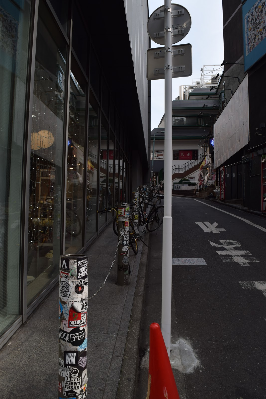 Shibuya backstreet with stickers on traffic sign and a traffic cone