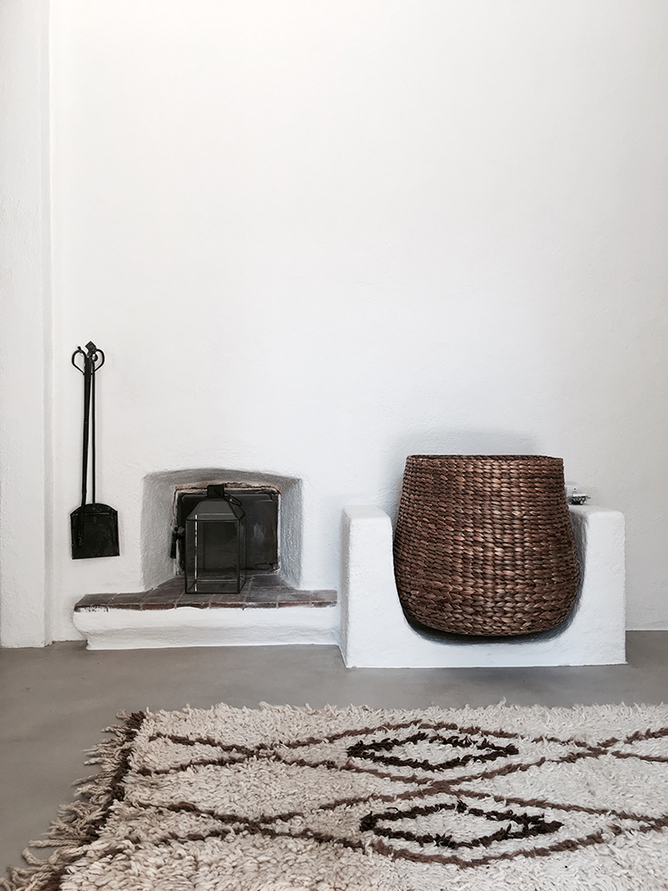 Villa Son Font in Mallorca | Minimalistic rustic fireplace and large rattan firewood basket